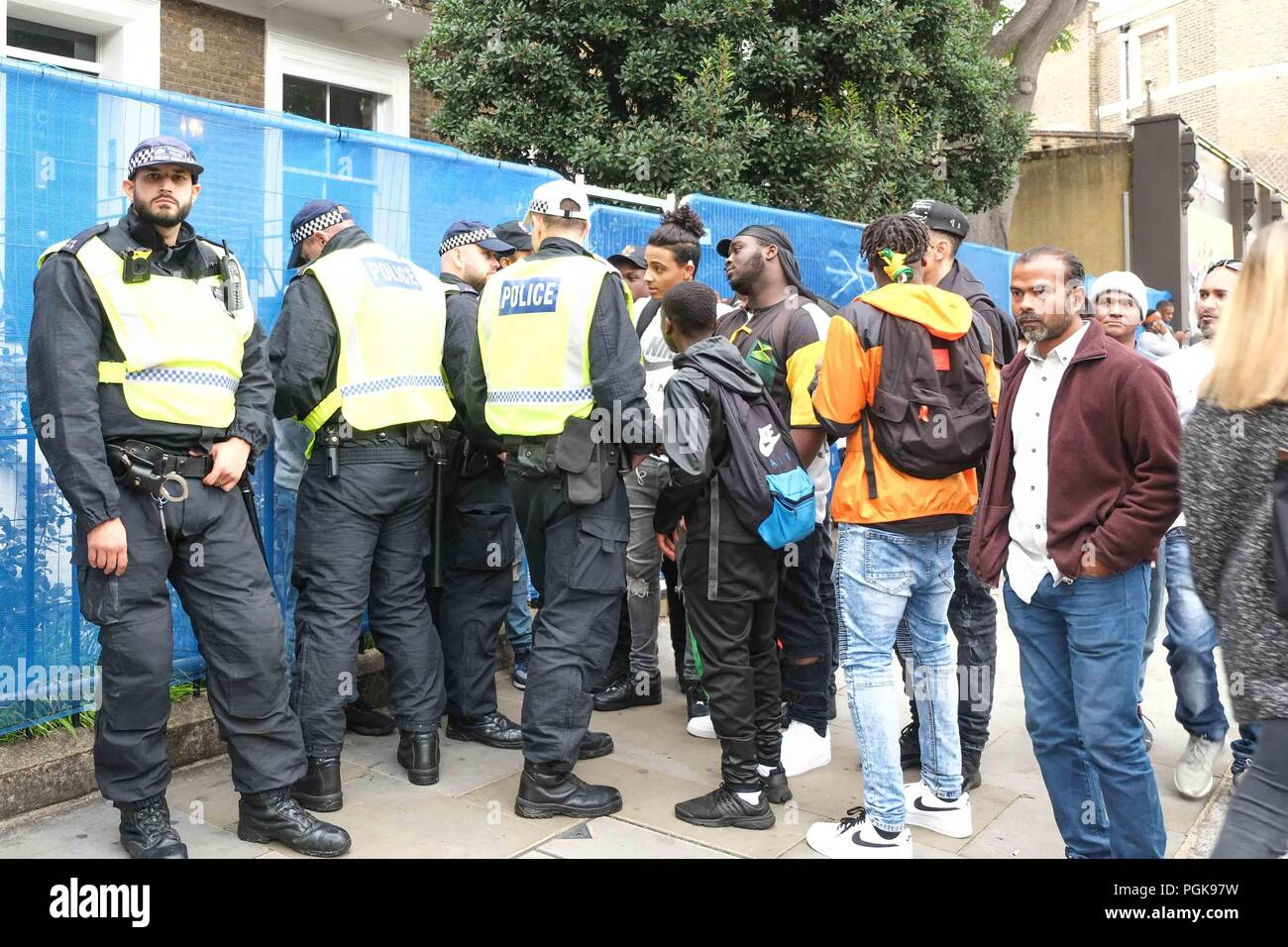 London, UK. 27th August 2018. Met police stop and search young men on the second day of  Notting Hill Carnival. The second day of the Notting Hill Carnival has been put under a Section 60 Order for the whole day. Section 60 gives police the power to search people.Credit: Claire Doherty/Alamy Live News - Stock Image