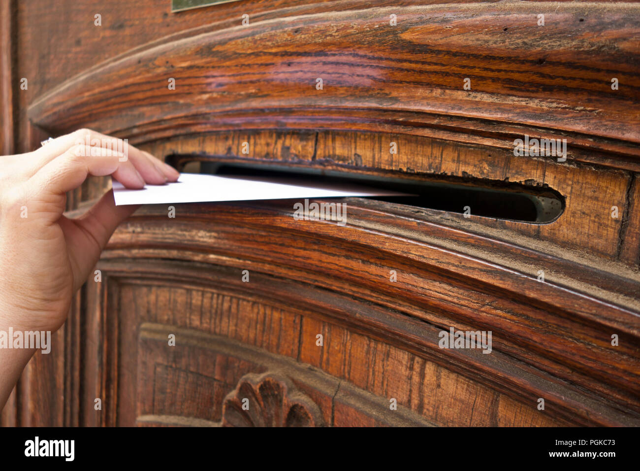 woman hand putting an envelope into a mail slot - Stock Image