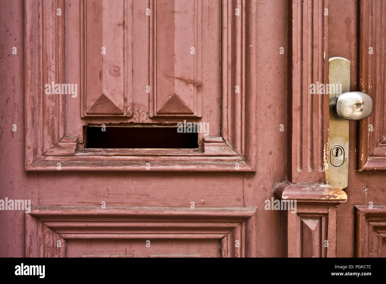 a mail slot in an old wooden door - Stock Image