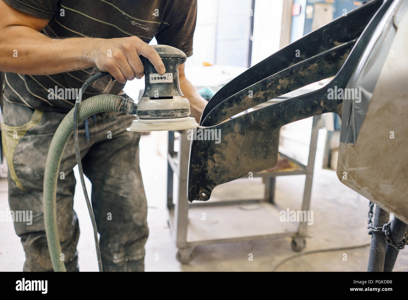 The mechanic works with a grinding machine. Garage painting car service. Repairing car section after the accident. - Stock Image