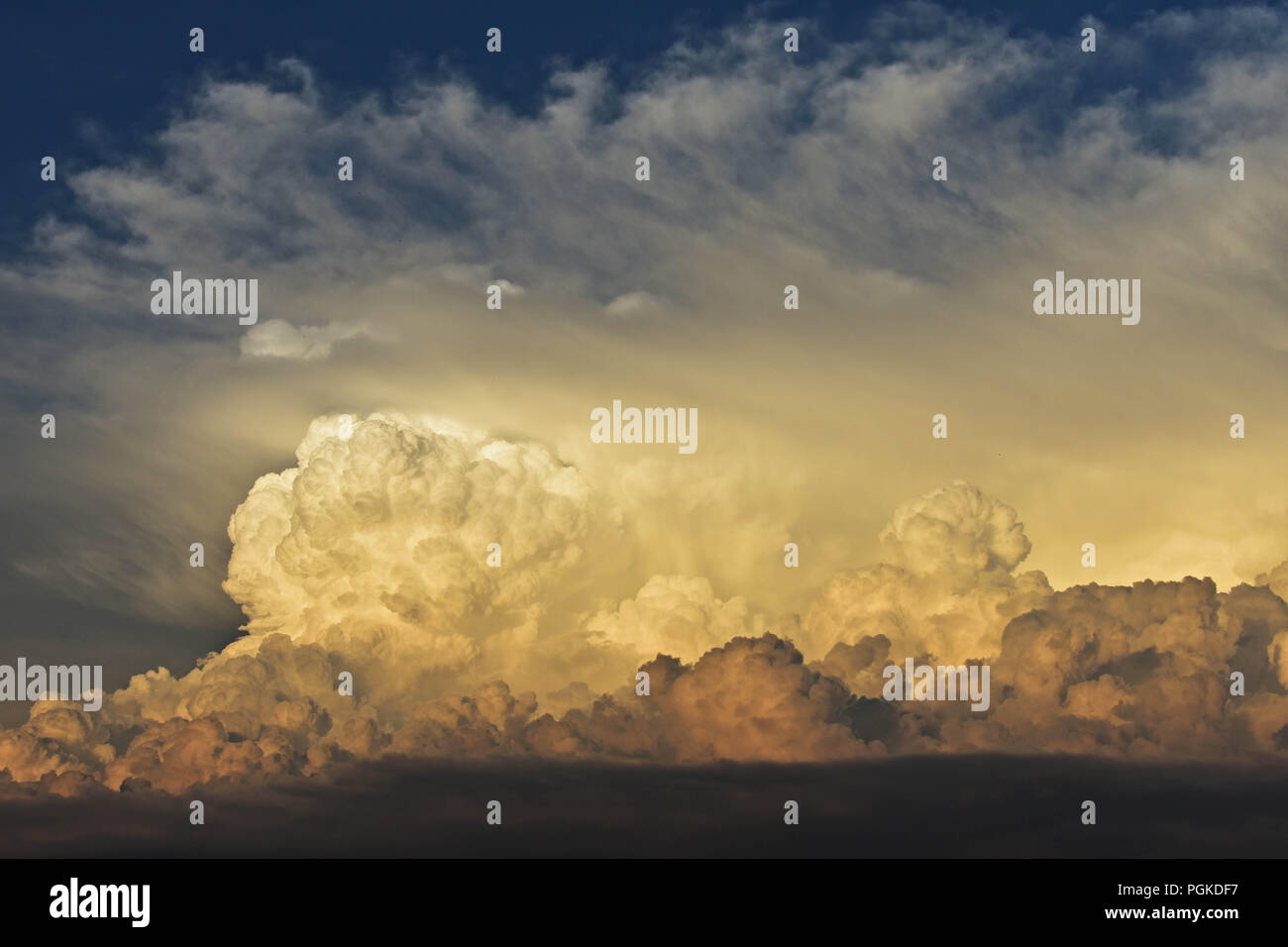 Gorgeous close up view of fluffy cumulus clouds with pink and yellow hues/ Above the clouds - Stock Image