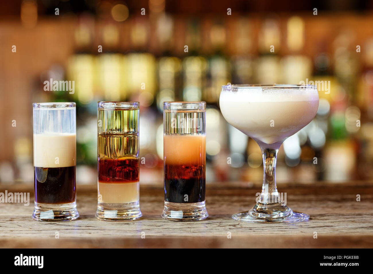 different club cocktails for men and women in different glasses stand on a bar counter on a blurred background of alcohol - Stock Image