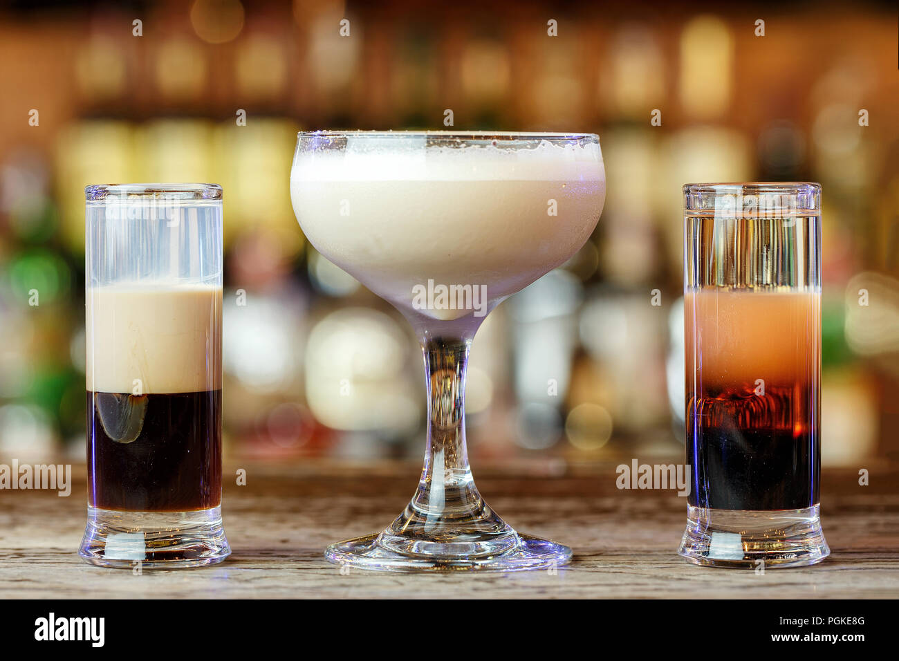 Different club cocktails in different glasses stand on a bar counter on a blurred background of alcohol - Stock Image