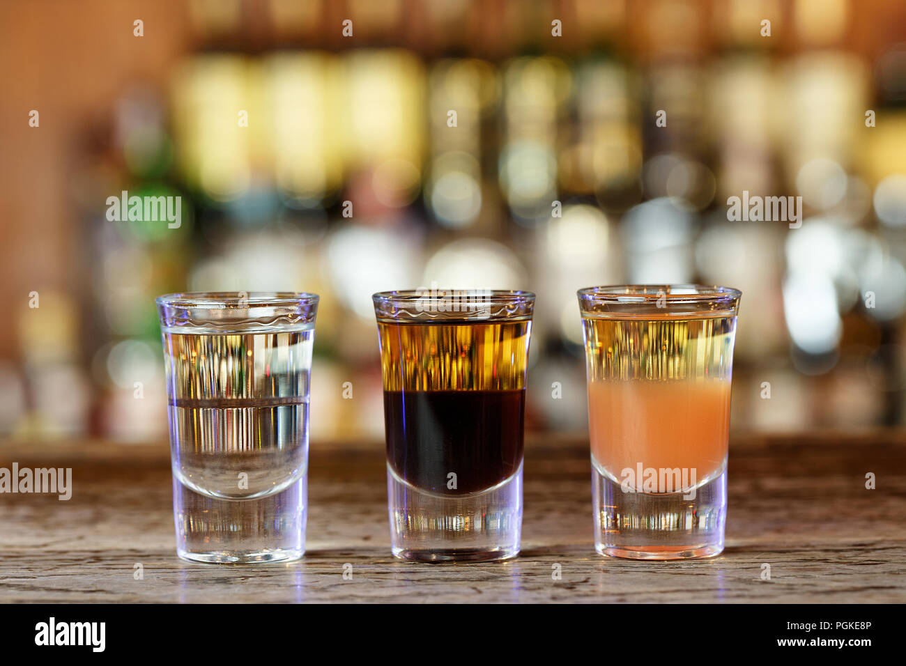 Different strong alcoholic cocktails shots in a nightclub on the bar counter - Stock Image