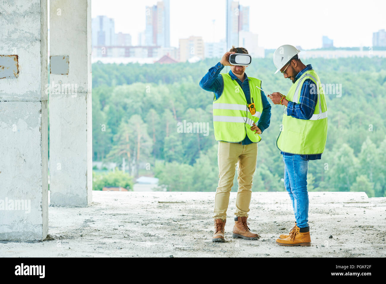 Full length portrait of two contemporary workers using VR to visualize projects on construction site, copy space - Stock Image