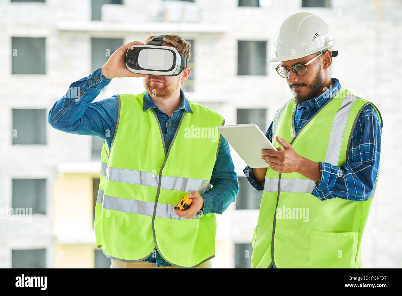 Waist up portrait of two contemporary workers using VR to visualize projects on construction site - Stock Image