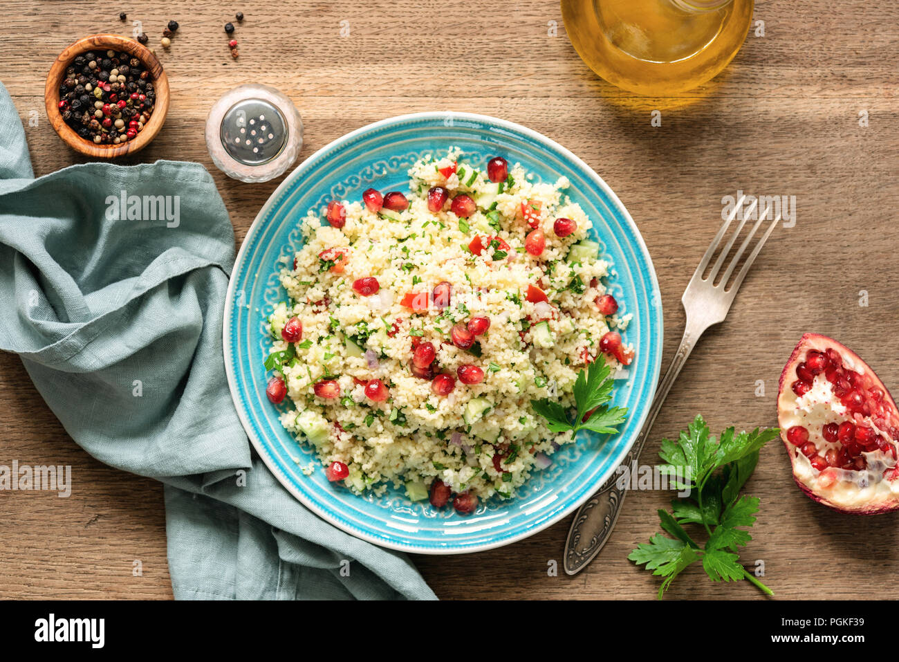 Couscous salad Tabbouleh with pomegranate seeds served on traditional turquoise plate. Arabic food - Stock Image