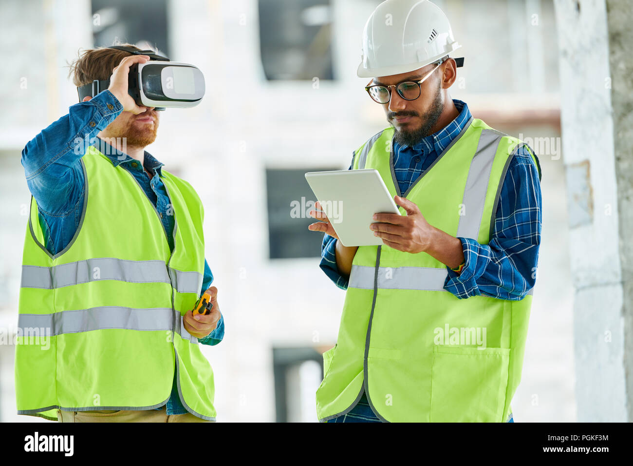 Waist up portrait of two contemporary workers using VR gear to visualize projects  on construction site - Stock Image