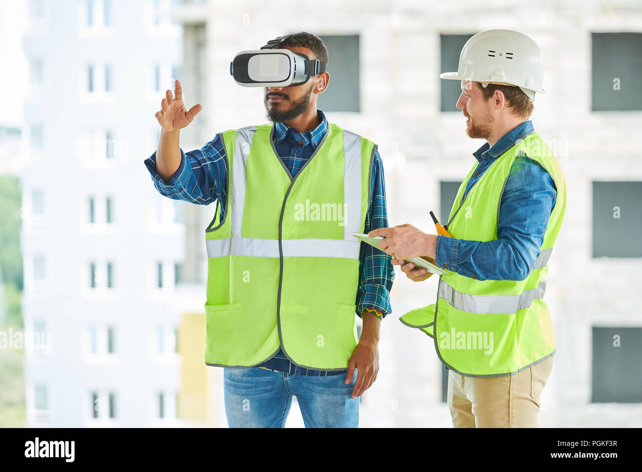 Waist up portrait of two modern construction workers using VR gear to visualize projects  on site, copy space - Stock Image