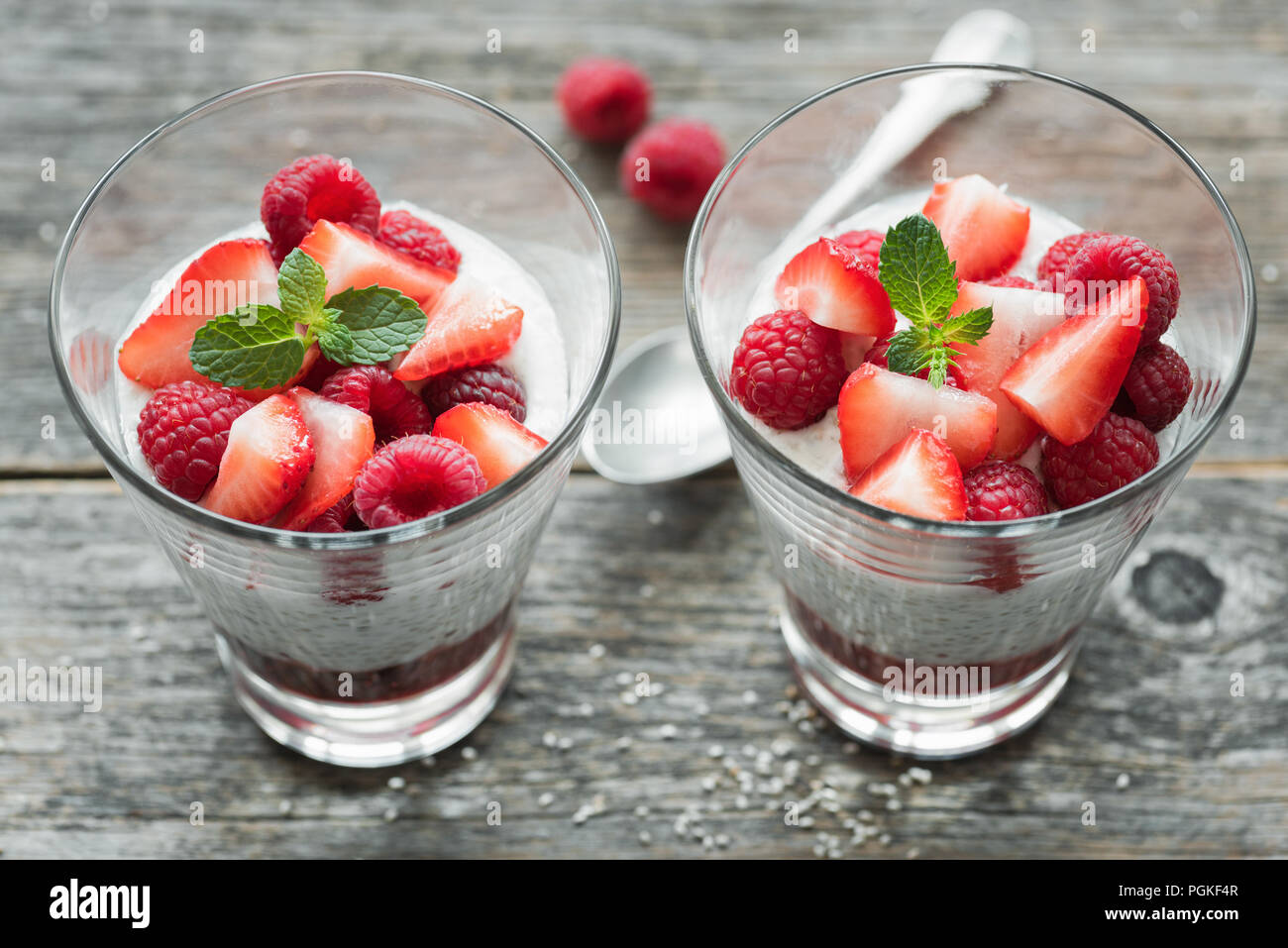 Protein chia pudding with fresh berries on wooden background. Top view, selective focus - Stock Image
