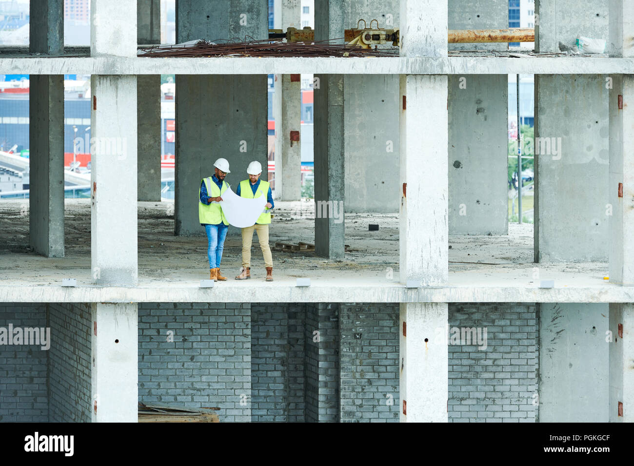 Wide angle view at two builders holding plans standing in unfinished ...