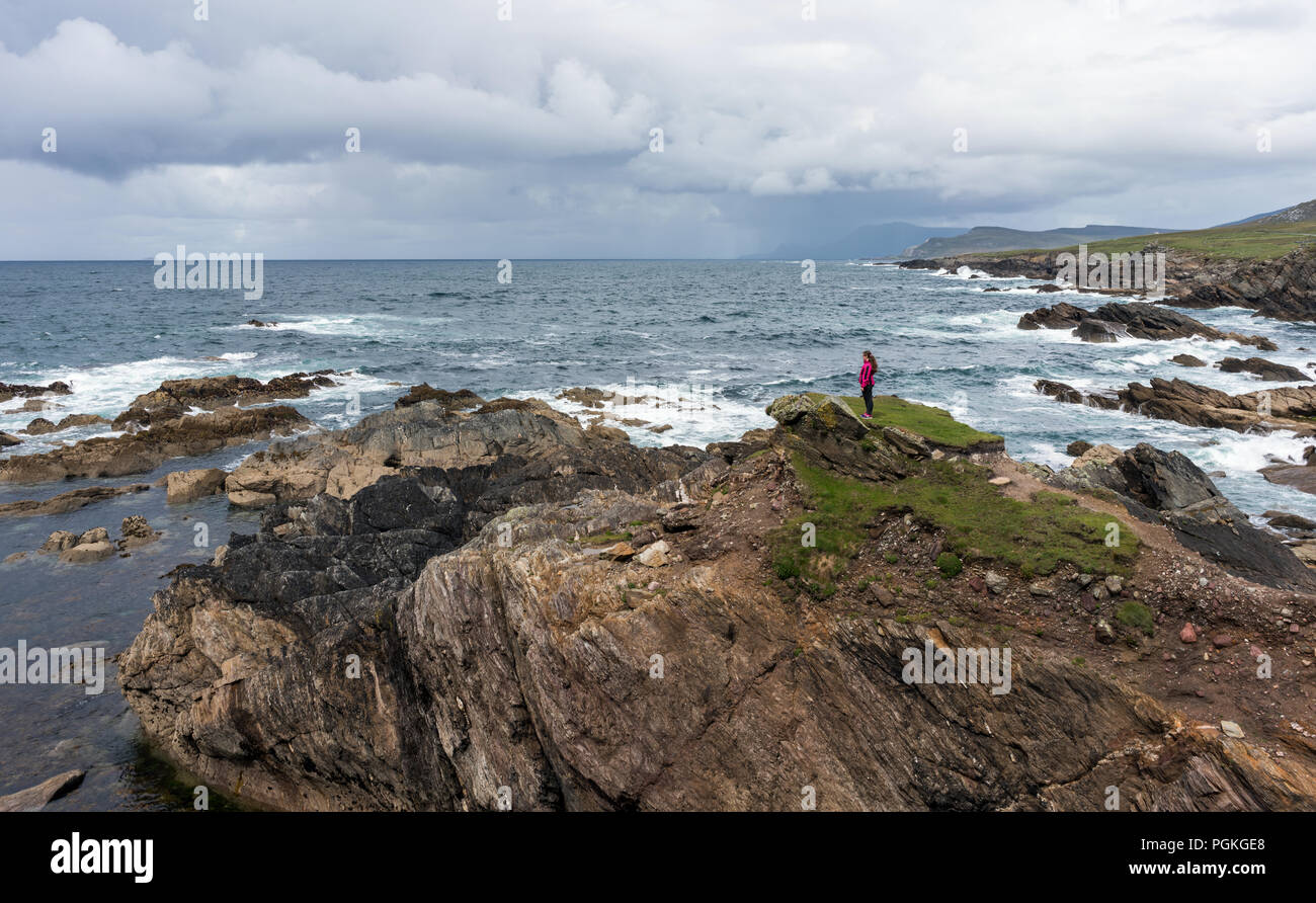 A little girl standing on a high cliff at Achill Island looking across the Atlantic Ocean. - Stock Image