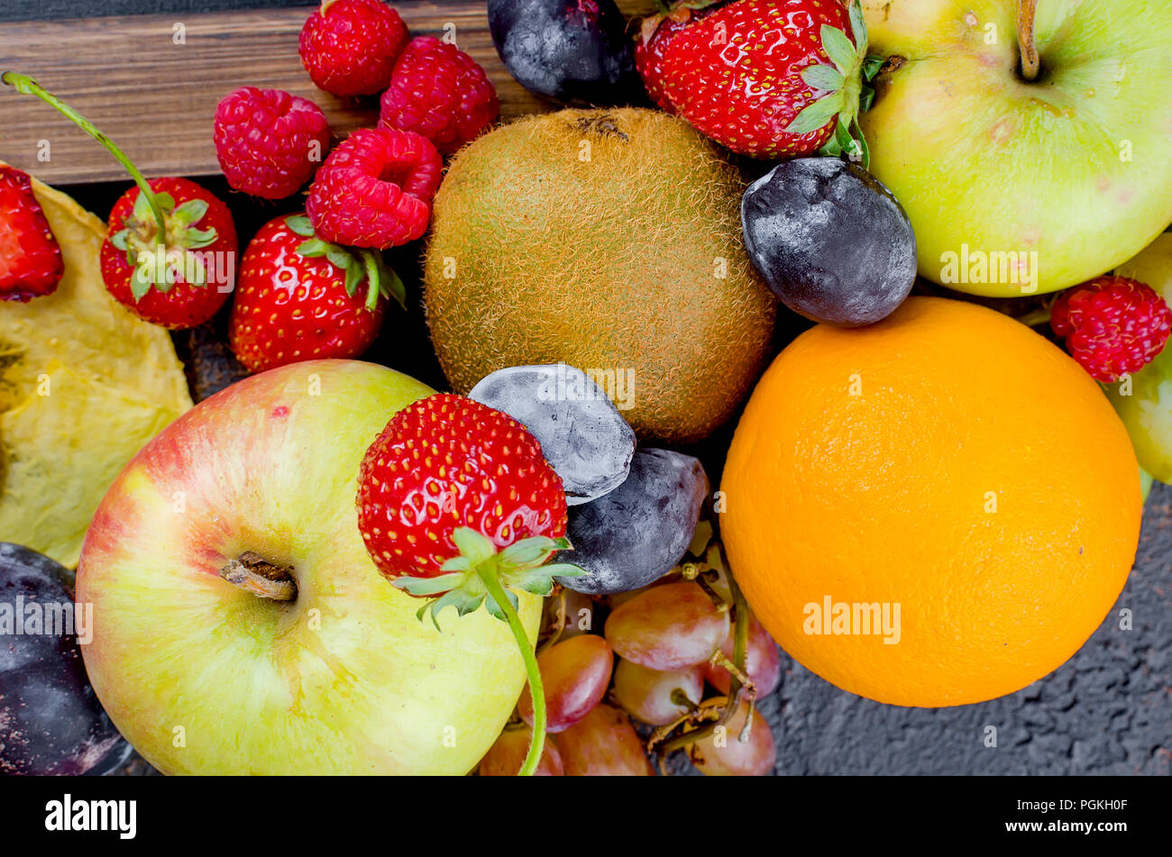 many different mixed seasonal ripe juicy fruits on dark background , concept of healthy and proper nutrition, snack, top view, copy space - Stock Image