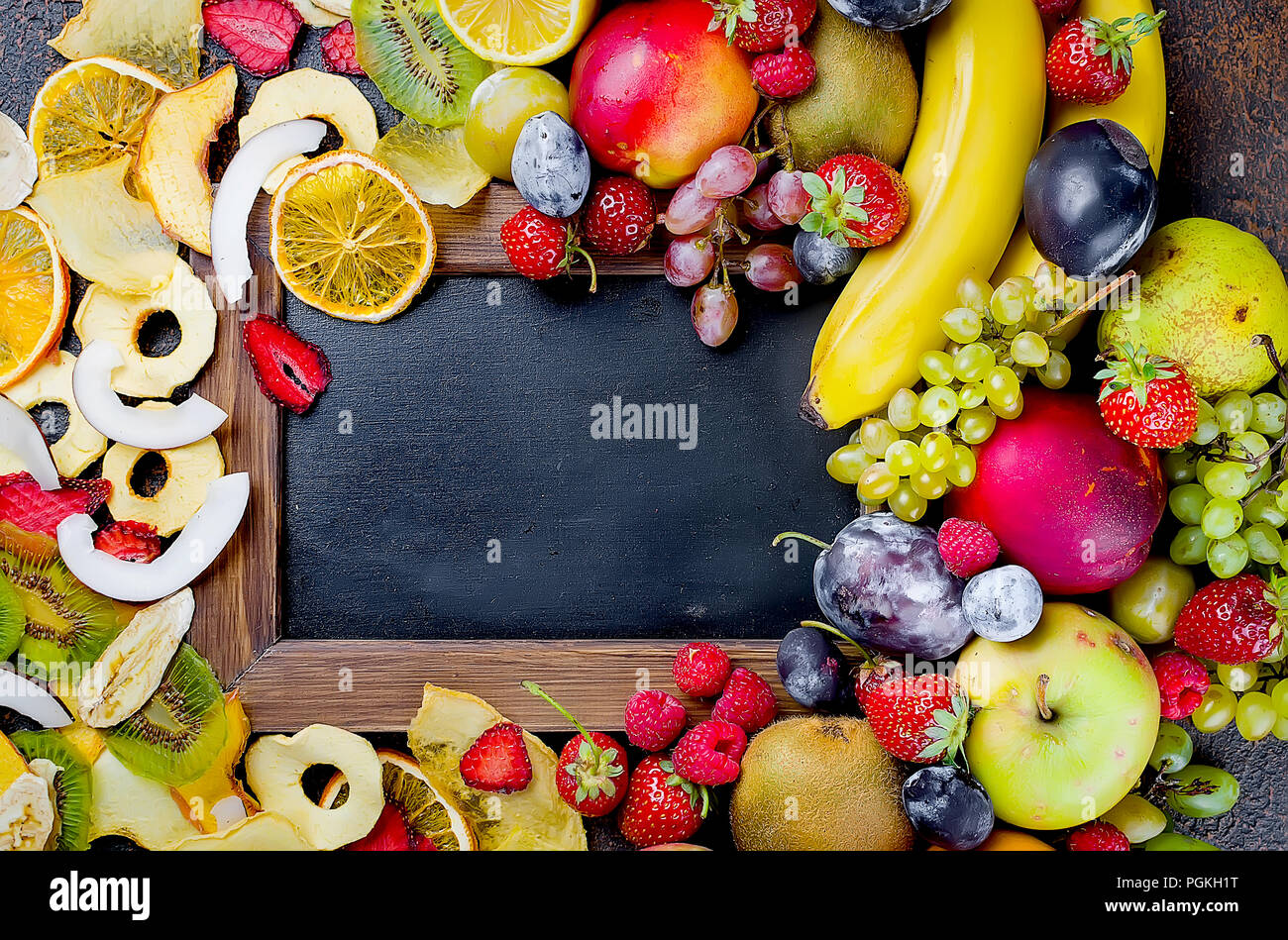 Raw ripe fruits and Fruit chips laid out around with an empty space for text on dark background , concept of healthy and proper nutrition, snack, top  - Stock Image
