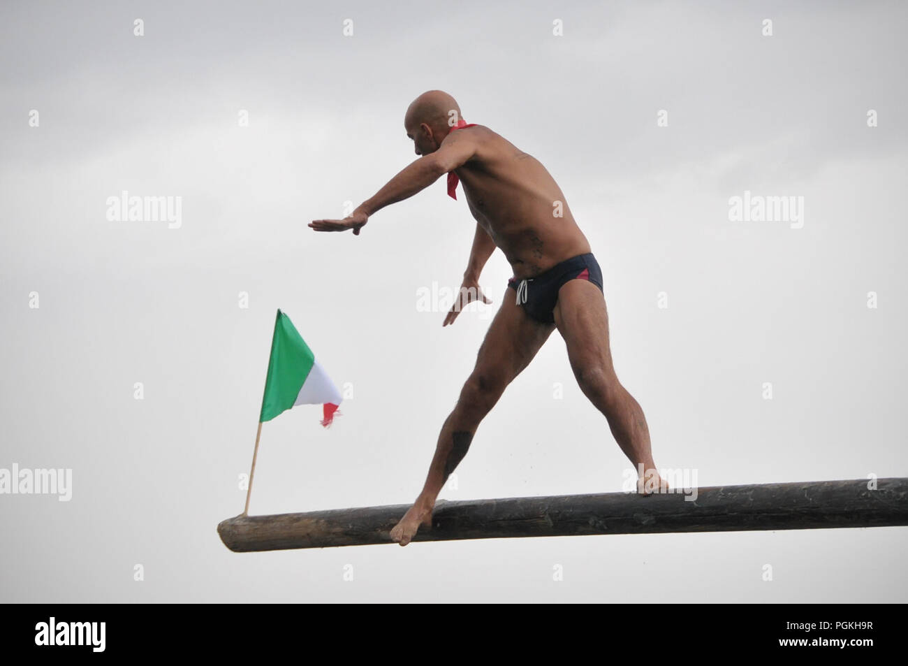 Pozzuoli, Italy. 26th Aug, 2018. The Pennone a Mare is a traditional competition that takes place between the fishermen of Pozzuoli on the Molo Caligoliano. The event is that the fishermen in the race must catch three flags fixed in the ends of a pole covered with soap and facing the sea. The race was postponed on August 15 in a sign of proximity to the city of Genoa after the collapse of the Morandi Bridge takes place today August 26th 2018. Credit: Paola Visone/Pacific Press/Alamy Live News - Stock Image