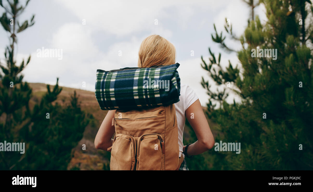 Woman carrying backpacks exploring the woods. Rear view of a female hiking in a forest. Stock Photo