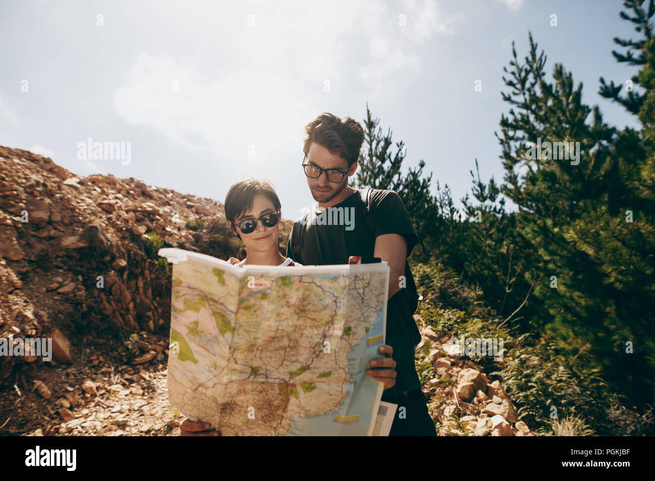 Man and woman holding a navigation map while hiking in a forest. Tourist couple using a map to find the route to their destination. - Stock Image