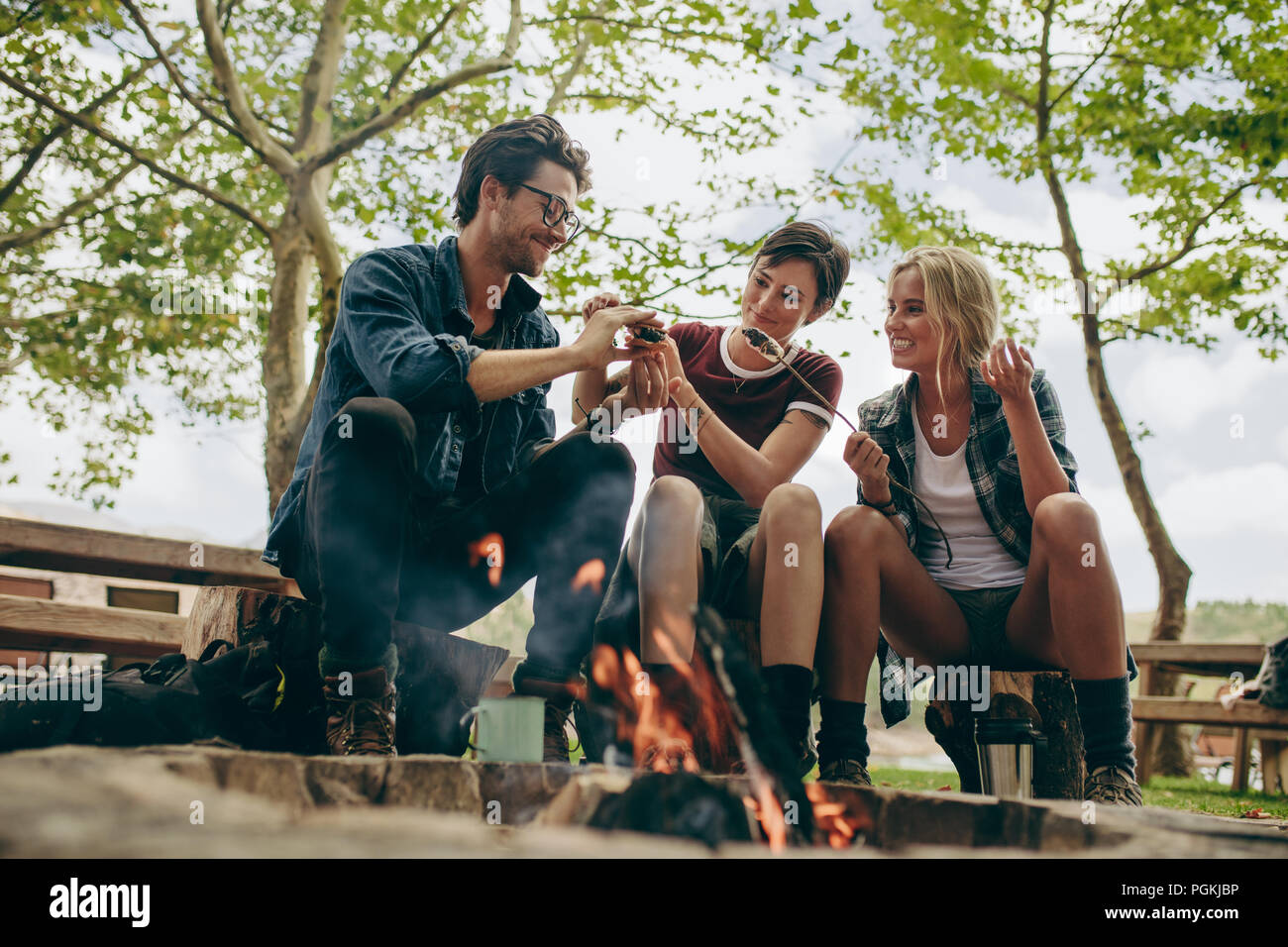 Smiling friends on holiday toasting food on bonfire. Friends making a sandwich with toasted marshmallows sitting outdoors in the countryside. - Stock Image