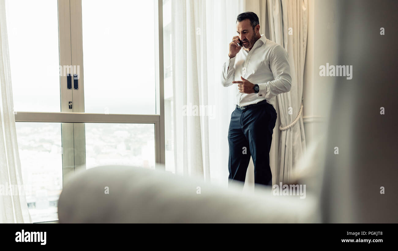 Male business traveler talking over cell phone while standing in a hotel room. Mature man in formal wear making a phone call from hotel room. Stock Photo