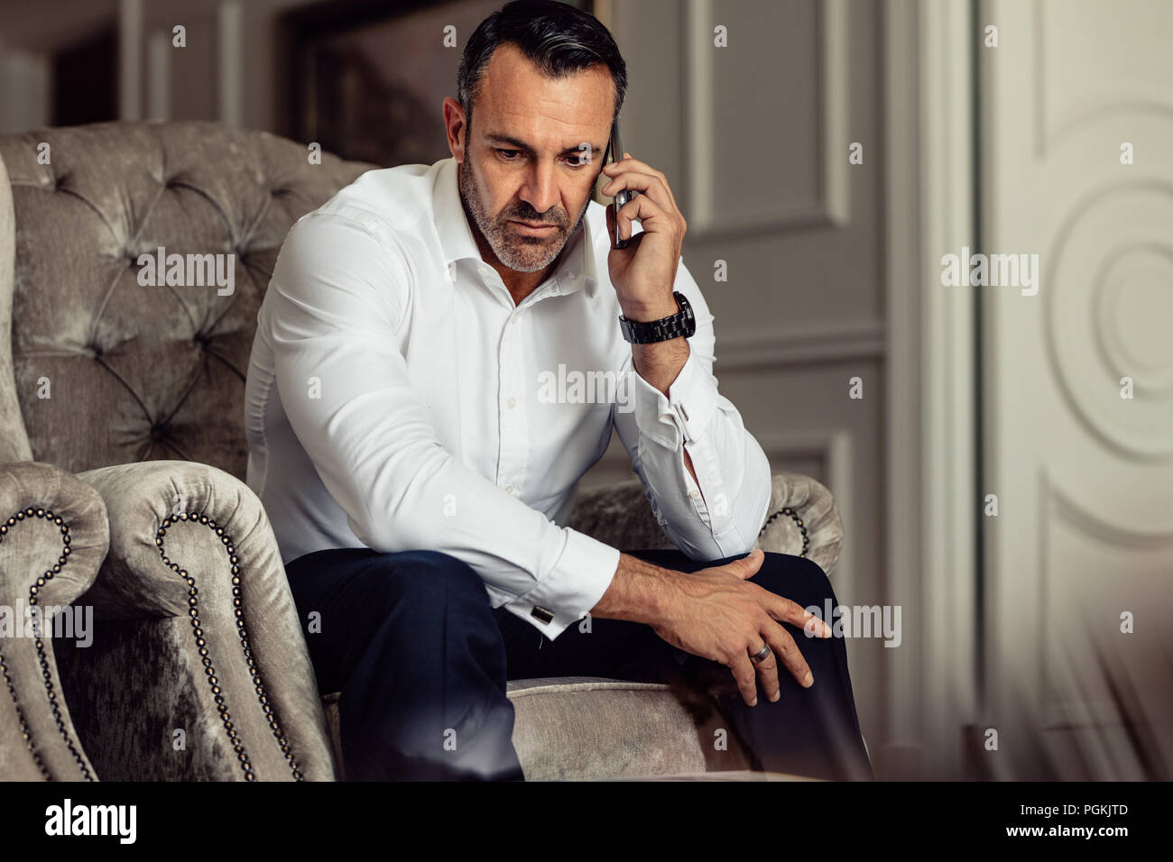 Businessman making a phone call after arriving in the hotel room. Man in formal wear sitting on chair and talking on smartphone. - Stock Image