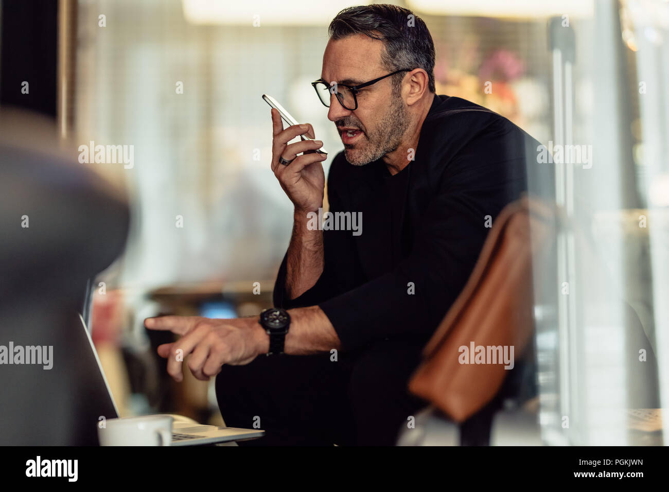 Mature businessman talking on phone while looking at laptop. CEO working while sitting in hotel foyer. - Stock Image