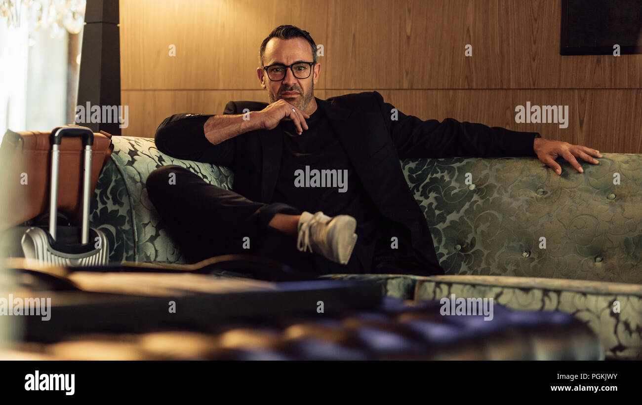 Portrait of handsome businessman sitting relaxed on sofa at hotel lobby with his luggage looking at camera. Male entrepreneur in business trip waiting - Stock Image