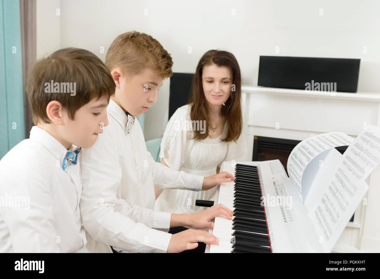 Kids studying at electric piano instrument, playing in tandem, teacher next to them - Stock Image