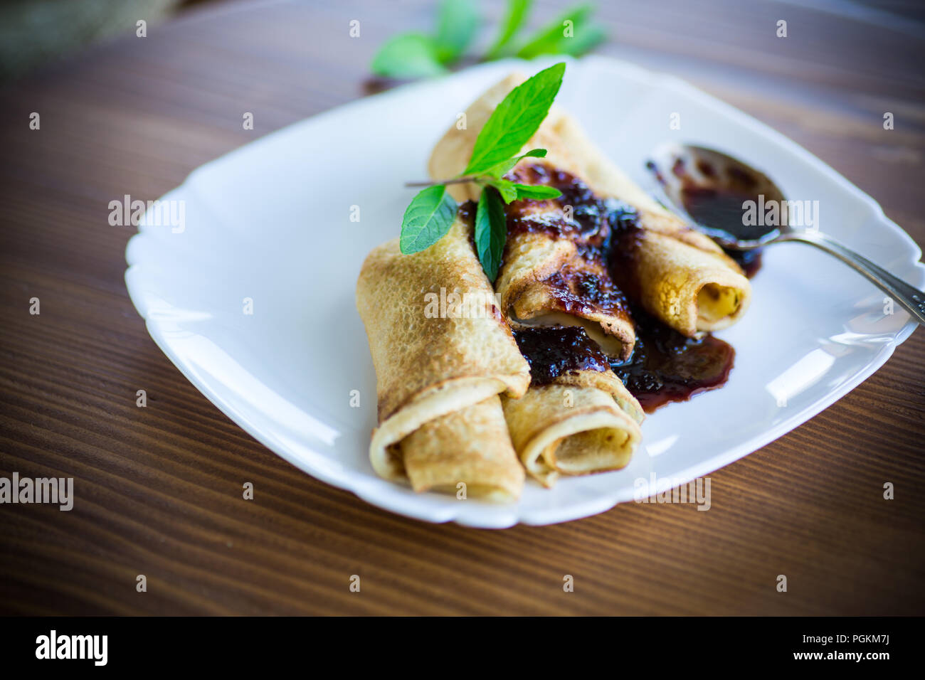 thin fried pancakes stuffed with jam in a plate on a wooden table - Stock Image