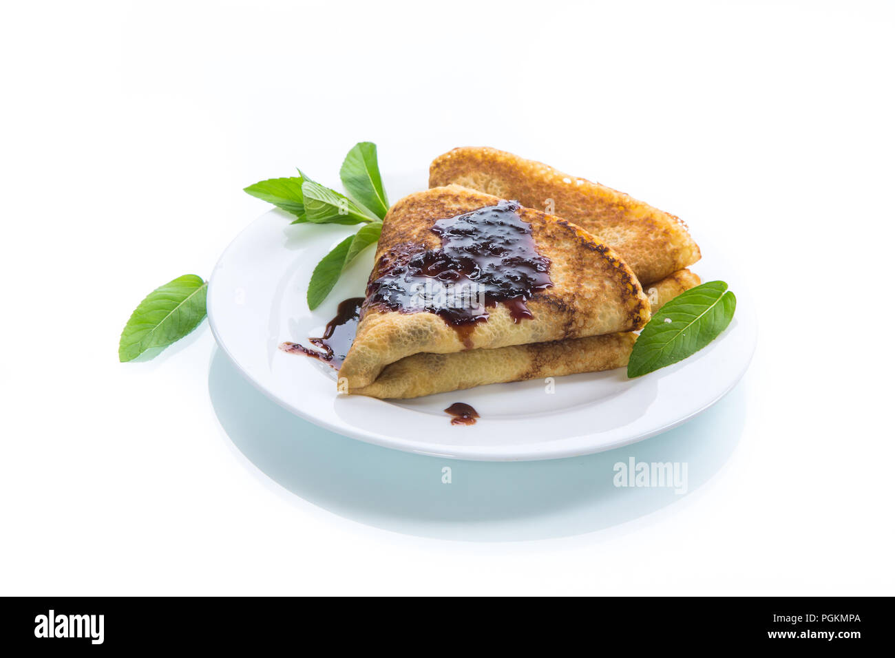 thin sweet pancakes folded in the form of a triangle with jam and a sprig of mint in a plate on a white background - Stock Image