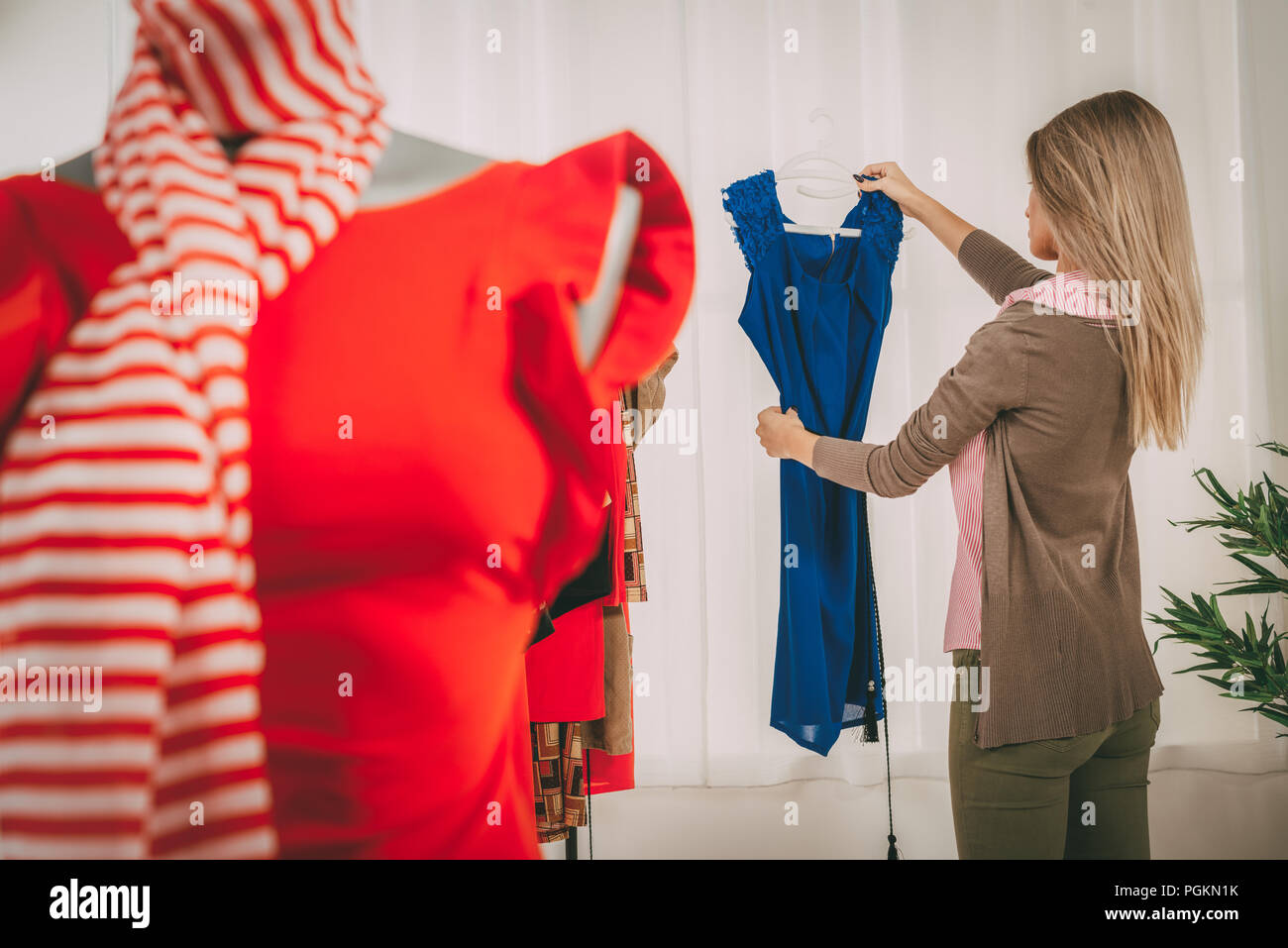 Fashion designer at the office looking dress. In the foreground you can see  a dress on mannequin. Selective focus. Focus on background. 45a7e602b