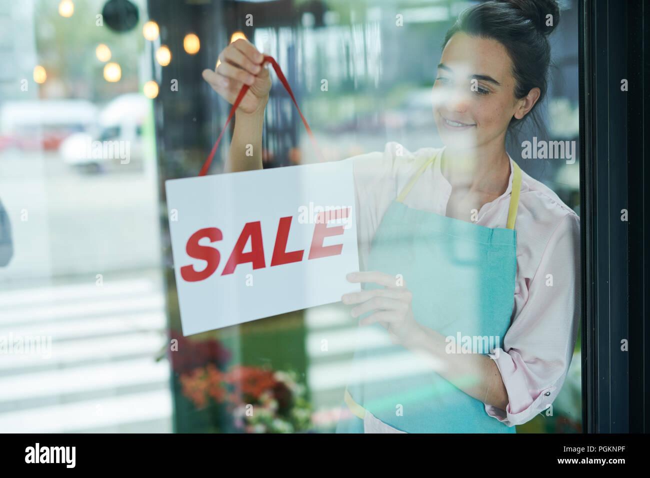 Waist up portrait of smiling female shopkeeper hanging SALE sign on door - Stock Image