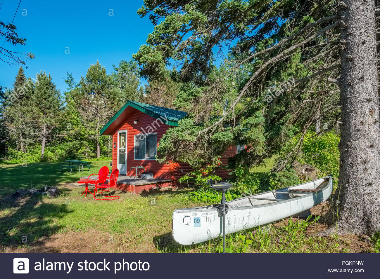 Canoe with electric motor is in front of a cabin located a short walk from Lake Superior, near Grand Marais, Minnesota, USA. Stock Photo
