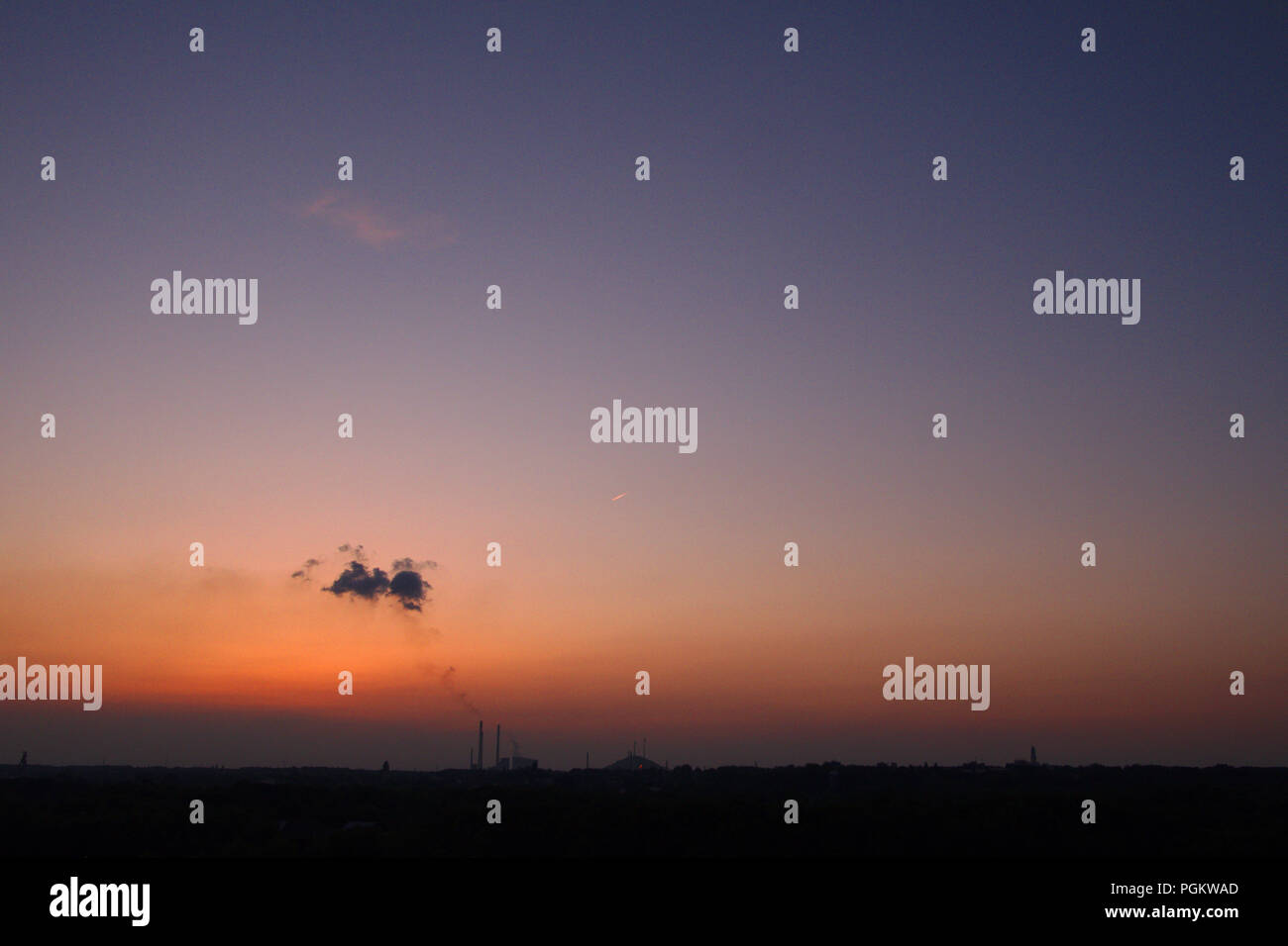 Puffy clouds from chimney stacks against a sunset. - Stock Image