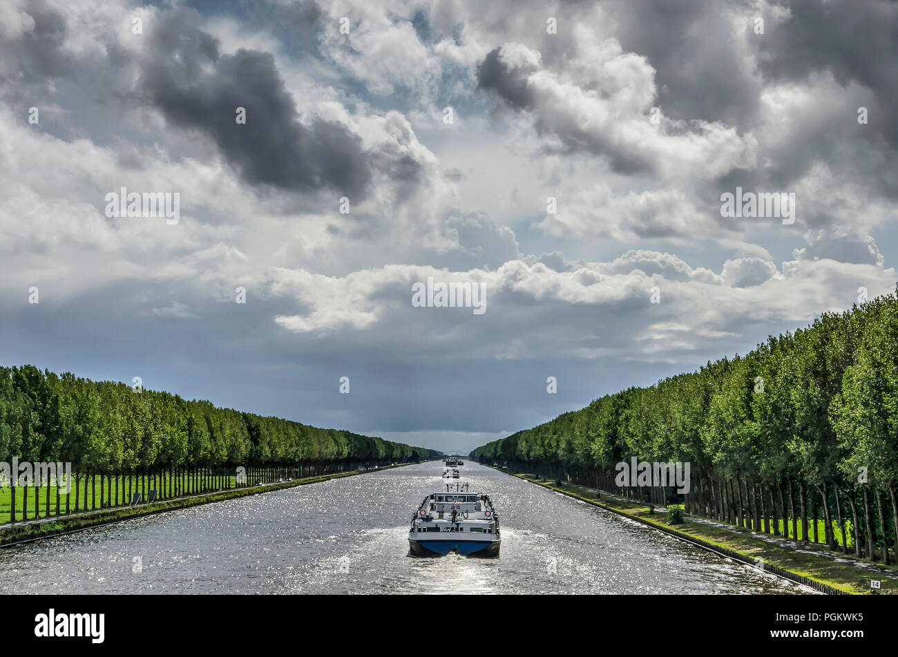 Central perspective of the long and straight Amsterdam-Rhine canal just south of Amsterdam, with inland barges and long lines of trees under a dramati - Stock Image