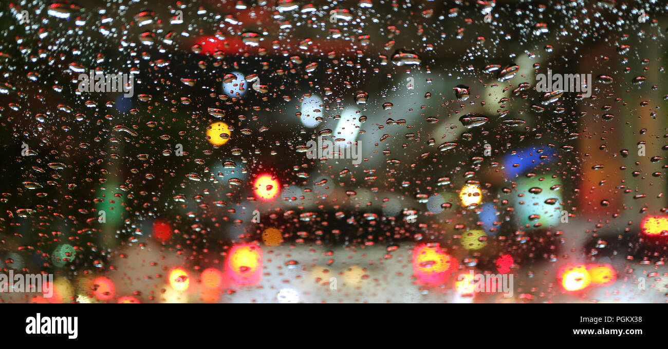 Blurred vehicle tail lamps viewed through water droplets on car windshield - Stock Image
