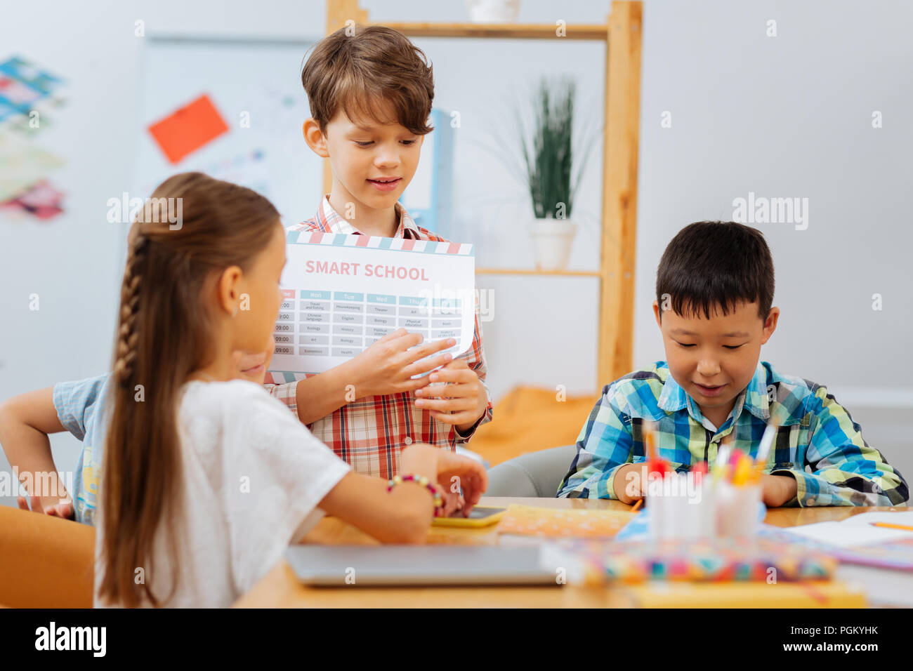 Attentive schoolboy explaining new material to the mates - Stock Image