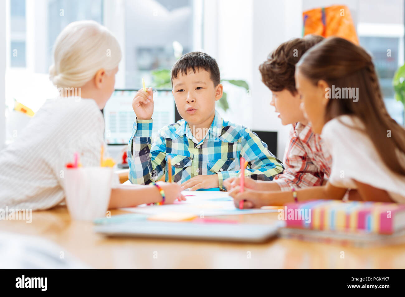 Smart schoolboy telling a story to his classmates - Stock Image