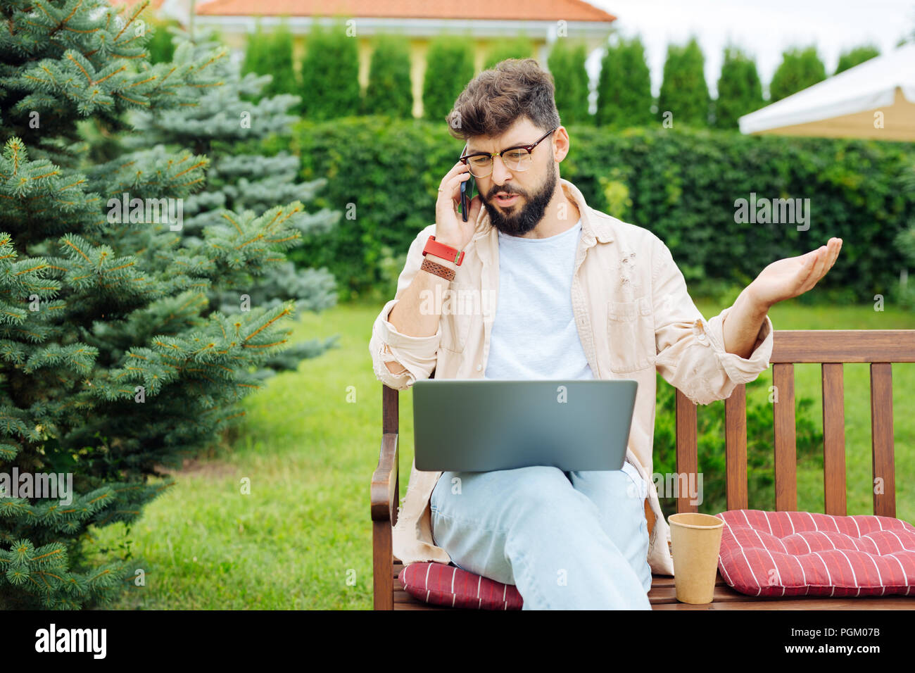 Bearded freelancer arguing with his colleague on the phone - Stock Image