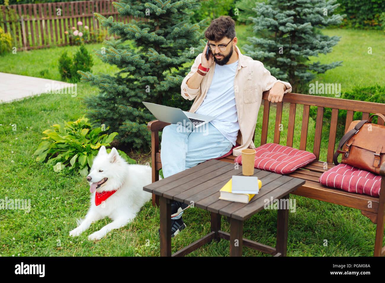 Stylish freelance copywriter reading his business e-mail - Stock Image