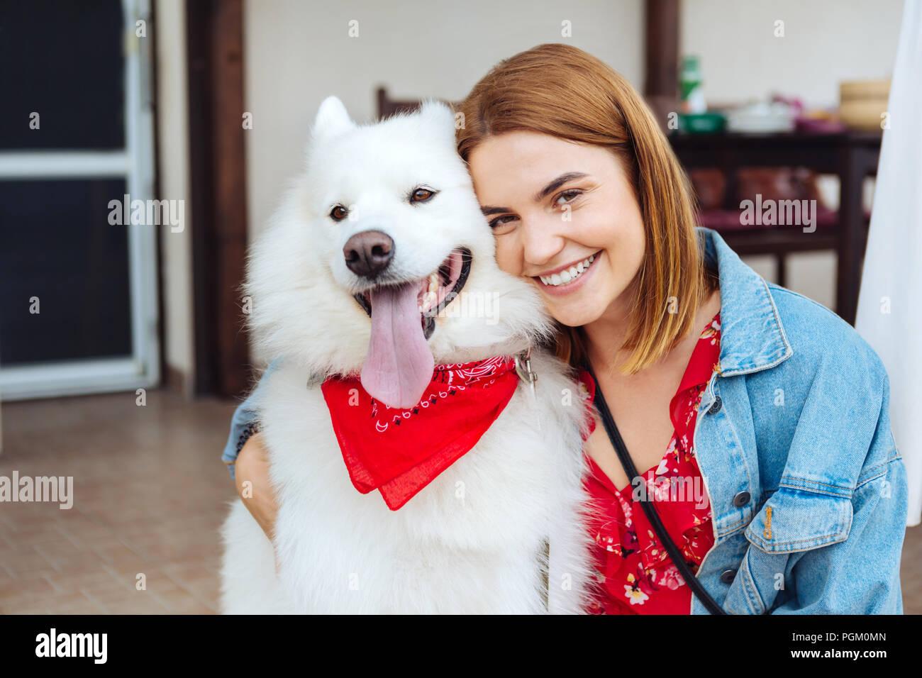 Dark-eyed woman smiling while hugging her cute husky - Stock Image