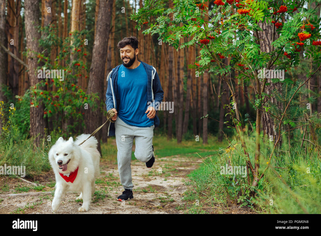 Bearded man wearing sport suit running with dog in the forest - Stock Image