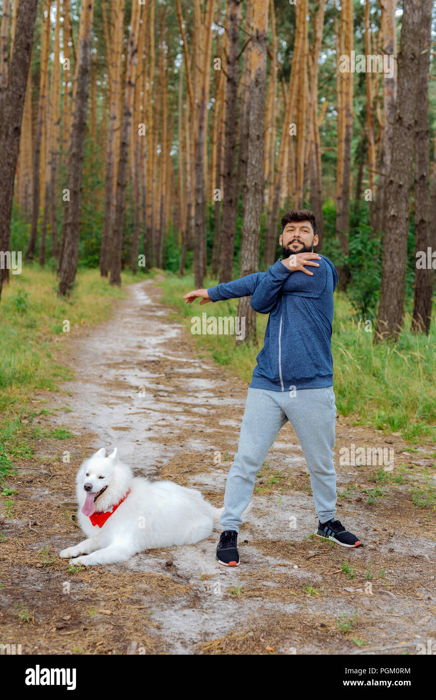 Dark-haired businessman stretching his arms before running in forest - Stock Image