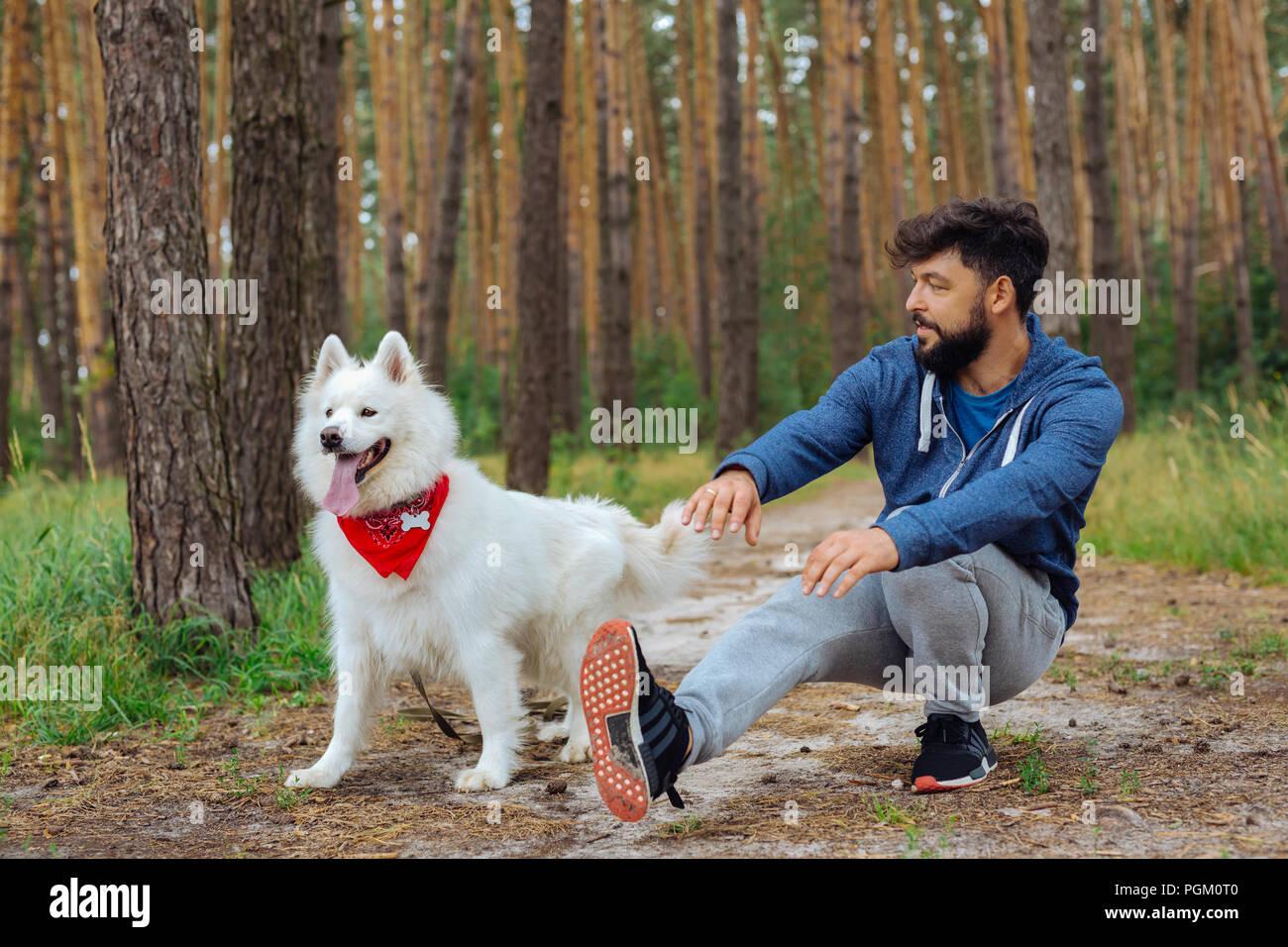 White fluffy dog standing near his owner doing sport - Stock Image
