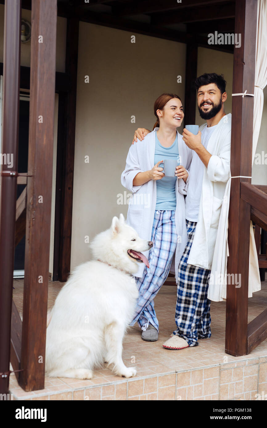 Bearded caring man hugging his wife spending nice morning together - Stock Image