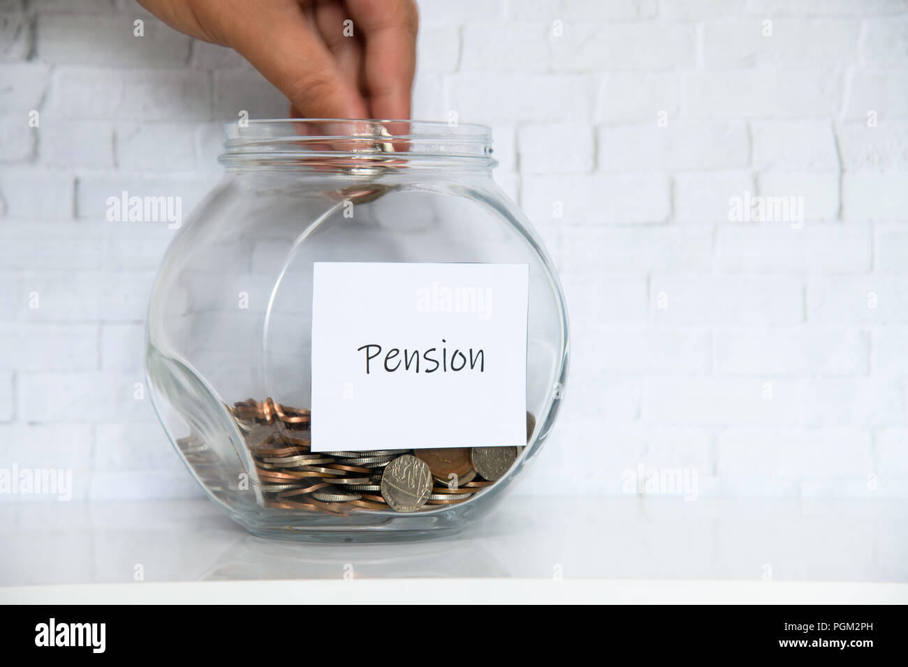 UK Money Jar on a white shelf in a household living room. Saving for Pension Concept - Stock Image