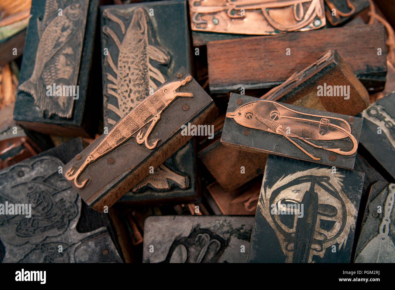 A selection of wood and metal printer's blocks featuring fishing lures and fish. From a collection of fishing tackle and sporting collectibles. North  - Stock Image