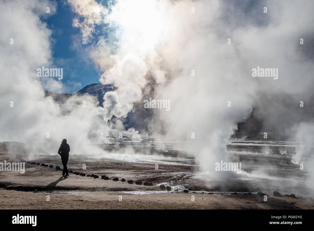 El Tatio geysers in Chile, Silhouette of a woman walking among the steams and fumaroles at sunrise - Stock Image