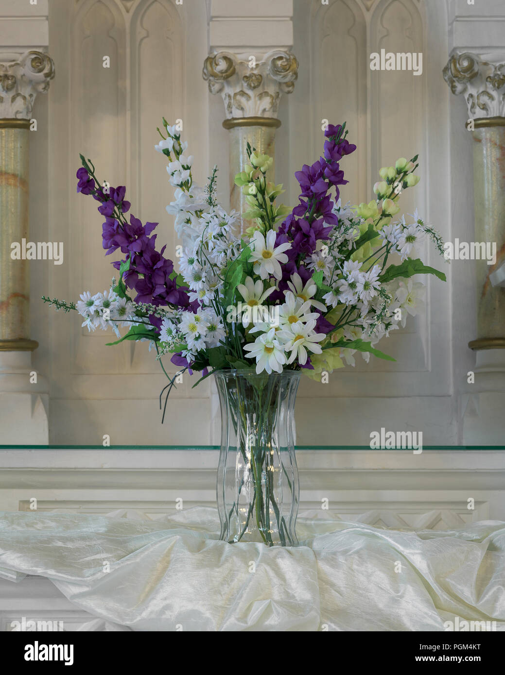 Long stemmed artificial flowers in class vase inside the St. Peter's Roman Catholic Church on Cabot Trail in Ingonish Beach, Nova Scotia - Stock Image