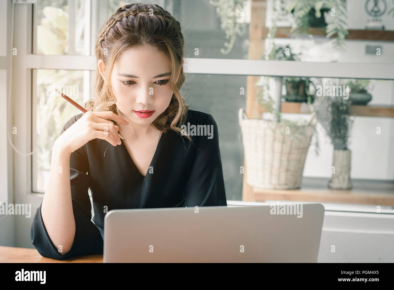 Beautiful Freelancer Woman working online at her home. - Stock Image