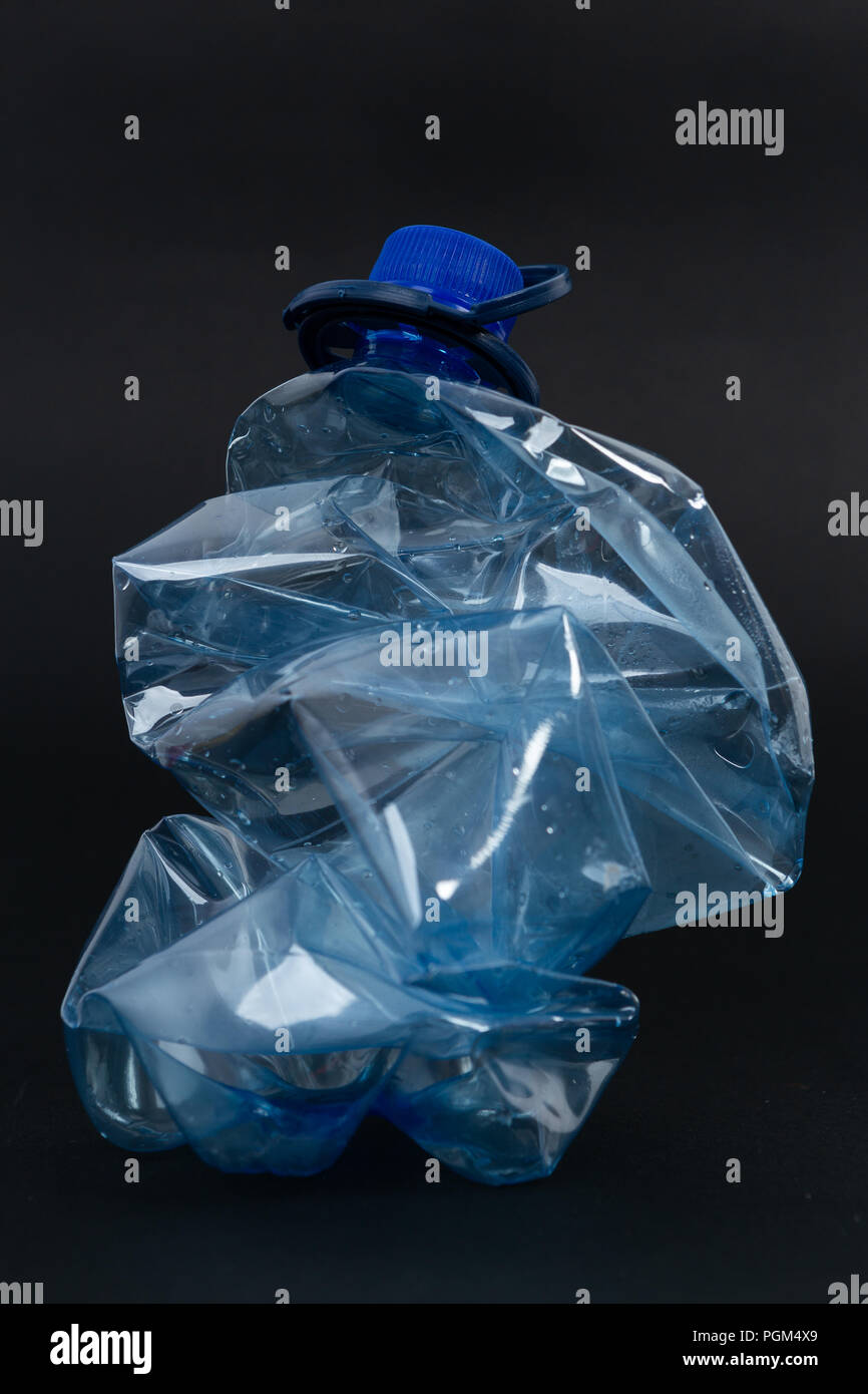 Crumpled recyclable plastic blue water beverage pet bottle as recycling single use pollution waste ecology concept isolated on black background - Stock Image